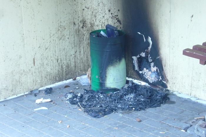 Podpalony pojemnik  na śmieci na przystanku autobusowym w Potulicach